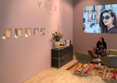 Wohnzimmeratmosphäre mit einer beigen Couch und zwei grauen Stühlen, bunter Teppich auf dem zwei Tische mit Drahtgeflecht stehen, Sideboard mit Blumen und Kaffeemaschine