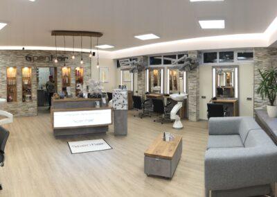 Friseursalon, Gesamtansicht des Friseursalons, diverse Bedienplätze mit Stühlen, Empfangstheke, die Steinwand mit integrierten Wandregalen, Wartebereich, Eiche Vinylboden