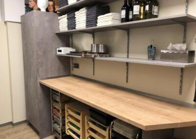 Friseursalon, Backup Raum, zu sehen sind Einbauschränke, ein Arbeitstisch und Regale, in den Regalen befinden sich Handtücher und Arbeitsutensilien, auf dem Schrank stehen Frisierköpfe