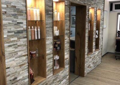 Mit Echtstein verblendete Wand mit eingelassene Produktregalen aus Holz. Verblender sandfarben. Die Regale mit integrierten Lampen. Tür aus braunem Holz. Logo des Studios an Wand
