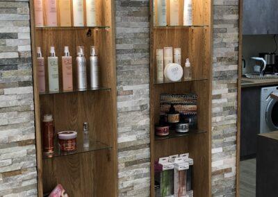 mit Echtstein verblendete Wand mit eingelassenen Produktregale. Regale sind aus Holz, Verblender sandfarben. Regale haben eingebaute Lampen. In Regalen stehen Haarpflegeprodukte