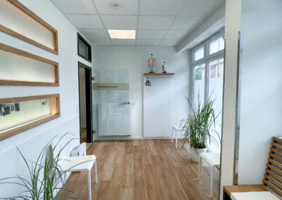 helles Wartezimmer einer Arztpraxis mit bodentiefen Fenstern