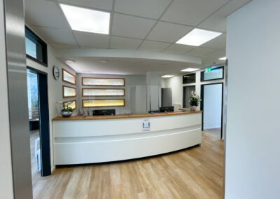 Geschwungene Empfangstheke mit Aufsatz und Beleuchtung, seitliche und rückseitige Arbeitsfläche, Hygieneschutz Acrylscheibe, Dekofenster beleuchtet