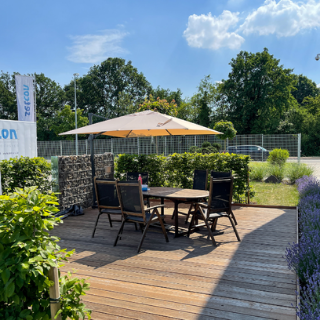 Sitzbereich auf Holzterasse mit Sonnenschirm, Tisch und Stühlen bei setcon Event & Expodesign GmbH