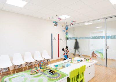 Wartezimmer, weiße Stühle, Garderobe, Spieltisch mit Spielteppich, Bücher, Kinderspielzeug, über Tisch hängt ein Baby Mobile, Wartebereich und der Flur durch gläserne Tür getrennt