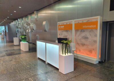 BASF Hauptversammlung, Foyer mit Raumtrenner, Acryl Trennwandmodule mit dimmbarer RGB-LED Beleuchtung, davor beleuchtete Theke und beleuchtete Blumenkästen