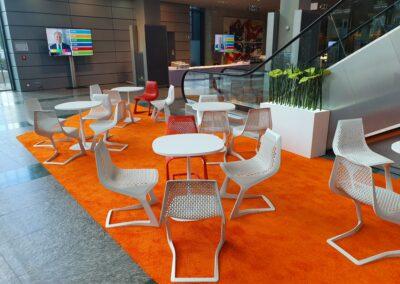 BASF Hauptversammlung, Foyer, Sitzecken mit weißen Tischen und weißen und roten Stühlen aus Metallgeflecht auf orangefarbenem Hochfloorteppich, Monitore auf Stelen