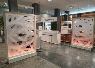 BASF Hauptversammlung, Empfangshalle mit Raumtrenner, Acryl Trennwandmodule mit dimmbarer RGB-LED Beleuchtung, Registrierung mit Theken und Wegeleitsystem