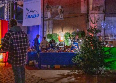 Weihnachtsmarkt in der Zeche Lohberg, beleuchteter Verkaufsstand der NABU mit Tannenbaum