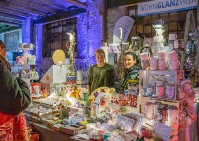 Weihnachtsmarkt in der Zeche Lohberg, beleuchteter Verkaufsstand mit zwei Verkäufern und einer Besucherin