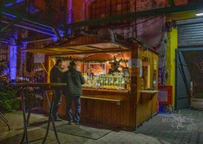 Weihnachtsmarkt in der Zeche Lohberg, beleuchteter Honig-Verkaufsstand aus Holz mit zwei Verkäufern und zwei Besuchern