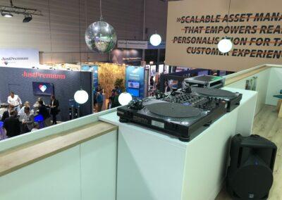 Messestand, Messebau, Messebauer, Kulissenbau, digitale Vermarktung, Networking, Discokugel, bunte Deckenleuchten, DJ-Set, DJ-Equipment, Boxen, Musik