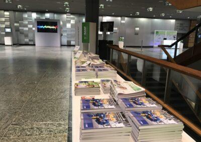 BASF Hauptversammlung, Eingangsbereich im Foyer mit beleuchteten Tischen für Bilanzbericht, Monitore auf Stelen