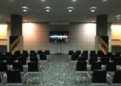 BASF Hauptversammlung, Foyer mit schwarzen Stühlen für Publikum, Monitor auf Stele