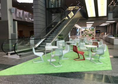 BASF Hauptversammlung, Foyer, Sitzecken mit weißen Tischen und weißen und roten Stühlen aus Metallgeflecht auf grünem Hochfloorteppich, Leuchtblumenkasten und Ausstellung