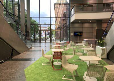 BASF Hauptversammlung, Foyer, Sitzecken mit weißen Tischen und weißen und roten Stühlen aus Metallgeflecht auf grünemHochfloorteppich, Monitore auf Stelen