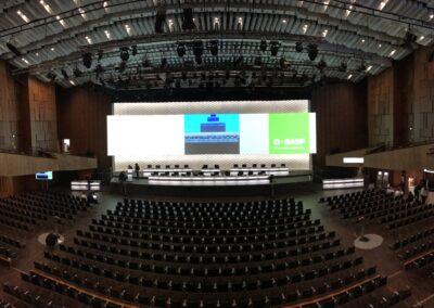 BASF Hauptversammlung, Bühne mit weißer OPERA Leinwand für Auf- Projektion, Tische mit Mikrofone und schwarze Drehstühle für Vorstandsmitglieder, Publikum Bestuhlung