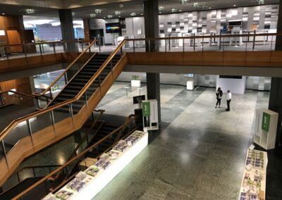 BASF Hauptversammlung, Eingangsbereich aus der Vogelperspektive, Foyer mit beleuchteten Tischen für Bilanzbericht, weiße Infostelen