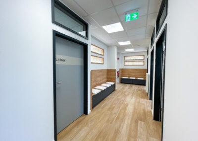 Flur mit Wartebereich, helles, modernes Ambiente, Sitznieschen, Oberlichtfenster, Labortür Eingang