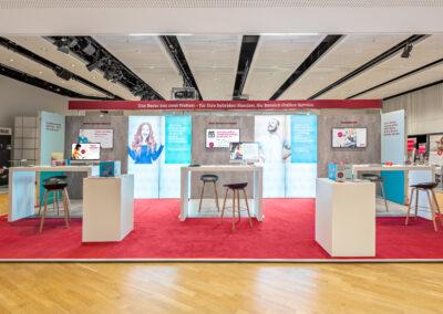 Großer ERGO Messestand mit rotem Teppichboden, Octawall Wandgrafiken, Monitore hängen an Messewand, weiße Brückentische mit schwarzen Barhockern