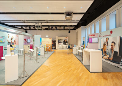 Großer ERGO Messestand mit grauem Teppichboden, Octawall Wandgrafiken, Monitore hängen an Messewand, Stehtische mit Barhockern, Prospektständer, weiße Brückentische