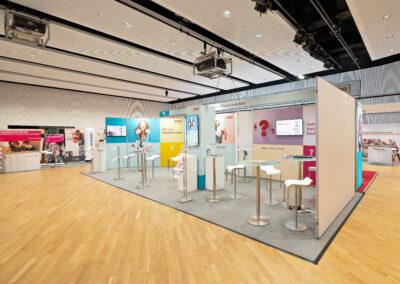 Großer ERGO Messestand mit grauem Teppichboden, Octawall Wandgrafiken, Monitore hängen an Messewand, Stehtische mit Barhockern, Prospektständer