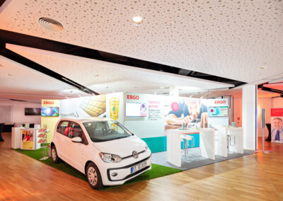 ERGO Partner-Messestand, Octawall Wandgrafiken, weiße Brückentische mit Barhockern, Teppichboden in Fußballrasen-Optik, grauer Teppichboden, Prospektständer, weißer VW, Gewinnspiel