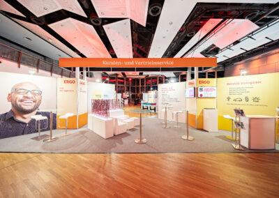 ERGO Messestand, Grauer Teppich, Weiße Loungemöbel mit Sichtschutz, Octawall Wandgrafiken, Monitore hängen an Messewand, Stehtische mit Barhockern, Counter und Prospektständer