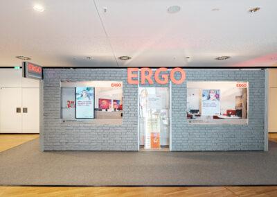 Begehbarer ERGO Messestand mit grauer Backsteinwand und grauem Teppichboden, Fernerkennung, Schaufenster mit Werbetafeln