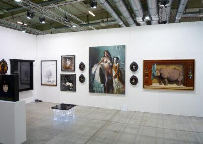 Blick auf eine Kunstwand der Art Fair Messe in Köln, an der Wand hängen dunkel gehaltene Bilder und andere Kunstwerke, in der Mitte vom Raum steht ein kleiner beleuchteter Tisch