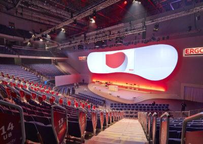 Fernansicht eines großen abschüssigen Saals mit vielen Sitzplätzen. Halbrunde Bühne überzogen mit weißem Teppich. Darauf ein Rednerpult. Über der Bühne hängt ein großer Screen