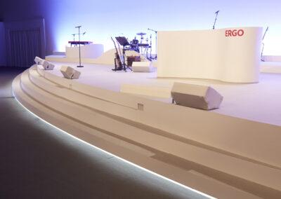 Schräge Bühnenansicht. Halbrunde Bühne ist überzogen mit weißem Teppich. Darauf steht ein Schlagzeug, eine Gitarre, ein Keyboard und ein Rednerpult