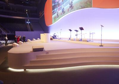 Seitenansicht einer Bühne. Bühne ist überzogen mit weißem Teppich. Auf der Bühne steht ein Rednerpult und mehrere Mikrofone