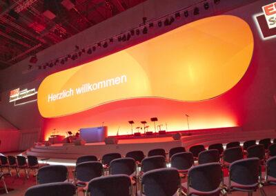 Frontalansicht einer Bühne. Bühne ist von hinten rot beleuchtet. Ein großer Screen hängt über der Bühne und ist beleuchtet. Auf der Bühne steht ein Rednerpult