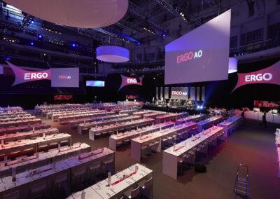 Großer Saal mit vielen Stehtischen, eingedeckt mit Geschirr. An der Decke hängen Lampen und Leinwandtücher mit Projektionsfolie. Auf einer Bühne spielt eine Band
