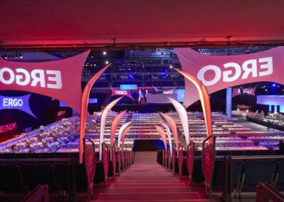 Fernansicht eines großen Saals mit vielen Stehtischen, eingedeckt mit Geschirr. Rechts steht eine Bühne mit Band. Links ist ein langer Buffettisch. An der Decke hängen große Banner