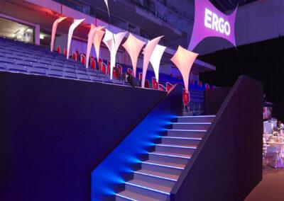 Ein beleuchtetes Treppenpodest mit Molton umspannt führt zur Tribüne. An der Decke hängen projektierte Banner befestigt mit Spannfixen. Am Rand des Tribünenaufgangs stehen Beachflags