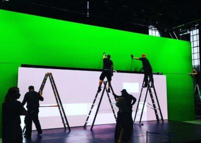 Aufbau eines Greenscreens, große Wand, Mitarbeiter, auf Leiter stehend, Wandaufbau, Messebau, Hintergrundplatzierung