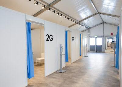 Impfzentrum Moers, Impfstraße mit weißen Impfkabinen mit Bestuhlung und blauen Vorhängen, Hygienestelen