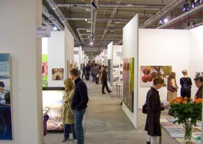 Blick durch einen Gang der Art Fair Messe in Köln, zu sehen sind mehrere Eingänge in die jeweiligen Ausstellungsräume, vereinzelt Exponate und mehrere Messebesucher