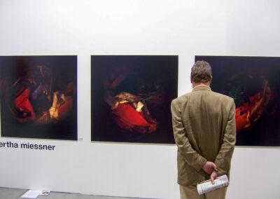 Blick auf eine Ausstellungswand der Art Fair Messe, an der weißen Wand hängen drei große quadratische dunkle Bilder, im Vordergrund steht ein die Bilder betrachtender Mann