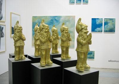 Ein Raum der Art Fair Messe in Köln, zu sehen sind sieben Exponate bestehend aus schwarzen, breiten Standfüßen und goldenen Zwergen mit bittender / betender Handhaltung
