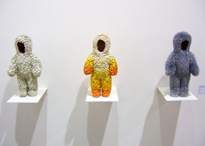 Exponate der Art Fair Messe in Köln, zu sehen sind drei kleine Staturen (von links nach rechts: weiß, gelb-orange, fliederfarben) in menschlicher Form. Alle jedoch ohne Gesicht.