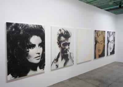 Ein Raum der Art Fair Messe in Köln, zu sehen sind sechs große, quadratische Gemälde verschiedener Schauspieler