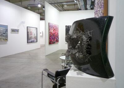 Blick durch einen Gang der Art Fair Messe in Köln, zu sehen sind mehrere Eingänge in die jeweiligen Ausstellungsräume und ein schwarzes Exponat im rechten Bildvordergrund