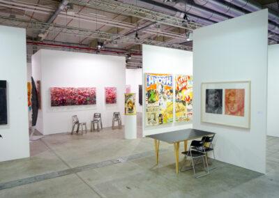 Blick durch einen Gang der Art Fair Messe in Köln, zu sehen sind mehrere Eingänge in die jeweiligen Ausstellungsräume und vereinzelt ein paar Exponate
