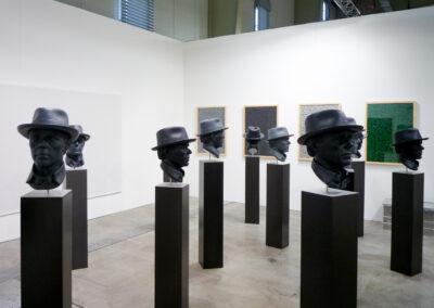 Ein Raum der Art Fair Messe in Köln, zu sehen sind 10 Exponate bestehend aus schwarzen, breiten Standfüßen und schwarzen Männerköpfen mit Hut als Ausstellungsstücke