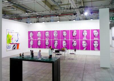 Ein Raum der Art Fair Messe in Köln, zu sehen sind 16 Gemälde mit knallig-lila Hintergrund und real gehaltenen schwarz-weiß Portraits diverser Schauspielerinnen