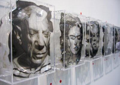 Exponat der Art Fair Messe in Köln, zu sehen sind 5 Glaskästen mit gewölbten Fotos menschlicher Köpfe – männlich wie weiblich