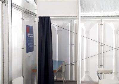 Trennwände aus Systembauteilen dienen als Impfkabine, darin steht ein Tisch und Stühle. Die Kabinen haben einen Vorhang